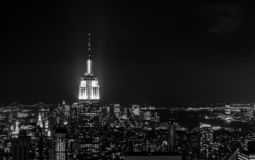 Sundown from the top of the rock - Empire State Building pinnacle brightly lit to the left of the frame - in black and white royalty free stock photography