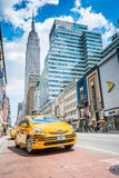 Empire State building and yellow taxi cab on the street Royalty Free Stock Image