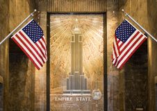 Empire State lobby. Art deco with two US flags royalty free stock images