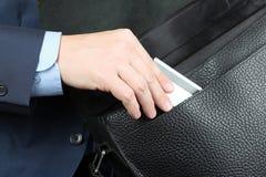 Emplacement d'homme d'affaires sur une chaise et sortir une carte de crédit f Image libre de droits