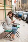 Emplacement de fille de voyage à la petite table basse dans la rue de la ville Photo stock