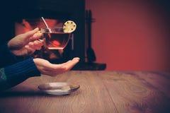 Emplacement de fille près de la cheminée avec une tasse de thé avec le citron Co Photo stock
