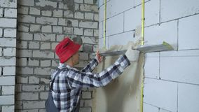 Emplastro de espalhamento do construtor na parede ventilada do bloco de cimento com régua da construção filme