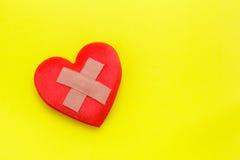 Emplastro ou curativo na forma vermelha do coração no fundo amarelo uso Foto de Stock