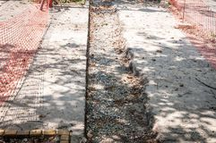 Emplazamiento de la obra de la acera para la reparación del sendero del asfalto rodeado y protegido con la red o la cerca anaranj foto de archivo libre de regalías