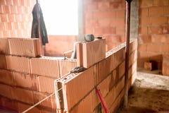 Emplazamiento de la obra con el albañil que construye la nueva casa con las paredes de ladrillo, cuartos interiores Imágenes de archivo libres de regalías