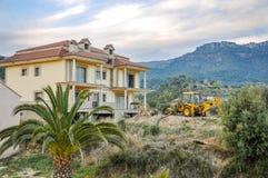 Emplazamiento de la obra con la nueva casa inacabada y el excavador amarillo Foto de archivo