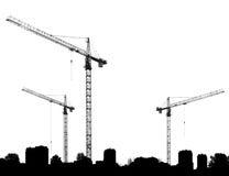 Emplazamiento de la obra con las grúas y los edificios de las siluetas Foto de archivo libre de regalías