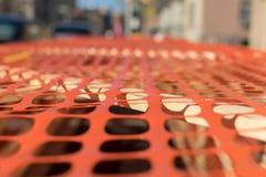 Emplazamiento de la obra cubierto por un pedazo de plástico anaranjado perforado, cubierto sobre un marco de madera simple hecho  fotos de archivo libres de regalías