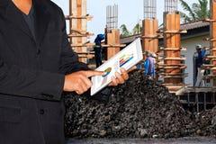 Emplazamiento de la obra del negocio, hombre de negocios usando la tableta y trabajadores de construcción borrosos del fondo foto de archivo libre de regalías
