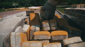 Emplazamiento de la obra, el trabajador de construcción Unloads la piedra que pavimenta de la carretilla Cámara lenta metrajes