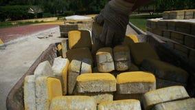 Emplazamiento de la obra, el trabajador de construcción Unloads la piedra que pavimenta de la carretilla Cámara lenta almacen de video