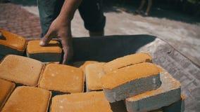 Emplazamiento de la obra, el trabajador de construcción Unloads la piedra que pavimenta de la carretilla Cámara lenta almacen de metraje de vídeo