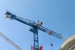 Emplazamiento de la obra Grúas y edificio alto de construcción bajo construcción contra el cielo azul Foto de archivo