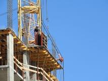 Emplazamiento de la obra grande, incluyendo varias grúas que trabajan en el complejo de la construcción, con un cielo azul claro fotos de archivo