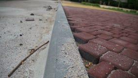 Emplazamiento de la obra, piedra de pavimentación coloreada del camino en un parque de la ciudad, proceso de construcción almacen de metraje de vídeo