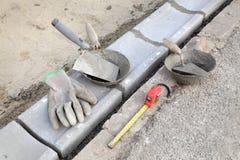 Emplazamiento de la obra, piedra del encintado y herramientas del albañil Foto de archivo