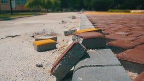 Emplazamiento de la obra, piedra de pavimentación coloreada del camino en un parque de la ciudad, proceso de construcción almacen de video