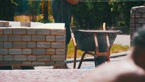 Emplazamiento de la obra, proceso de construcción, reparando la acera Trabajador que pone la piedra que pavimenta en un parque de metrajes