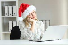 Empleado aburrido que trabaja en la oficina en la Navidad imagenes de archivo