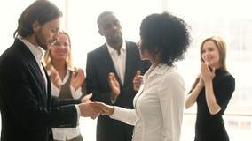 Empleado africano del apretón de manos del jefe de la compañía, promoviendo felicitando a la mujer joven negra almacen de metraje de vídeo