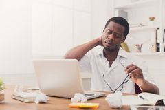 Empleado afroamericano con exceso de trabajo en la oficina, trabajo con el ordenador portátil Imagenes de archivo