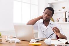 Empleado afroamericano con exceso de trabajo en la oficina, trabajo con el ordenador portátil Fotos de archivo libres de regalías