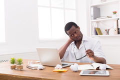 Empleado afroamericano con exceso de trabajo en la oficina, trabajo con el ordenador portátil Imagen de archivo libre de regalías