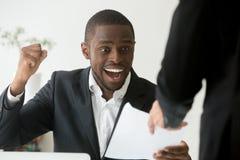 Empleado afroamericano emocionado que recibe el aviso sobre promoti foto de archivo libre de regalías