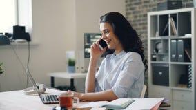 Empleado alegre de la muchacha que habla en el teléfono móvil que ríe usando el ordenador portátil en oficina almacen de video