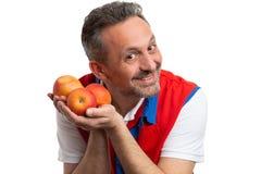 Empleado amistoso del hipermercado que muestra manzanas imagen de archivo