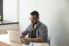 Empleado casual joven en el funcionamiento de vidrios en el ordenador portátil en oficina Fotografía de archivo libre de regalías