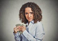 Empleado codicioso del negocio corporativo de la mujer que sostiene billetes de banco del dólar firmemente Imagen de archivo libre de regalías