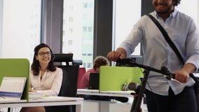 Empleado con la bicicleta que dice adiós al salir de la oficina en 5 P.M. almacen de video