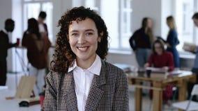Empleado corporativo de sexo femenino caucásico feliz en traje formal elegante con el pelo rizado que sonríe alegre en la oficina almacen de metraje de vídeo