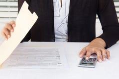 Empleado corporativo que trabaja en datos financieros en el lugar de trabajo Foto de archivo