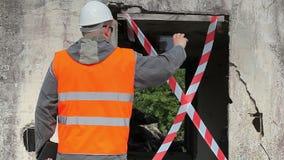 Empleado de la construcción filmado con el edificio dañado cercano de la tableta almacen de video