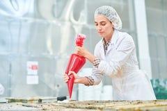 Empleado de la fábrica de la confitería que exprime el bolso de los pasteles imagenes de archivo