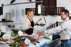 Empleado de la tienda que sonríe vendiendo pescados frescos y los mariscos enfriados imagen de archivo libre de regalías