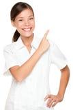 Empleado de mujer del balneario que señala en el backgroud blanco Imagenes de archivo