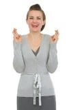 Empleado de mujer feliz con los dedos cruzados Fotos de archivo libres de regalías