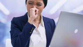 Empleado de oficina agotado que trabaja en el ordenador portátil que siente soñoliento y que bosteza, sobrecarga metrajes