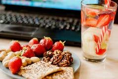 Empleado de oficina con el ordenador portátil, el bocado sano, agua con la fresa y el pepino imagen de archivo libre de regalías