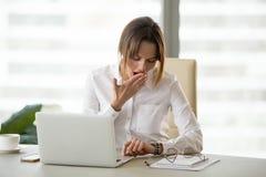 Empleado de sexo femenino agotado que comprueba tiempo en el reloj en oficina imagen de archivo