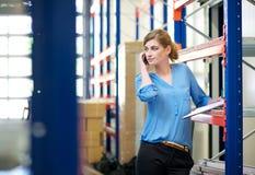 Empleado de sexo femenino casual del almacén que habla en el teléfono móvil Foto de archivo