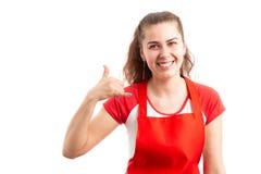 Empleado de sexo femenino del hipermercado o del supermercado que hace gesto de la llamada fotografía de archivo