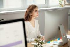 Empleado de sexo femenino enfocado atractivo que trabaja en la mesa en coworki Imagen de archivo libre de regalías