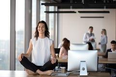 Empleado de sexo femenino feliz que medita en la tabla en oficina imagen de archivo
