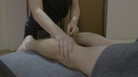 Empleado de sexo femenino hermoso del balneario que da un masaje terapéutico intenso al hombre joven - metrajes