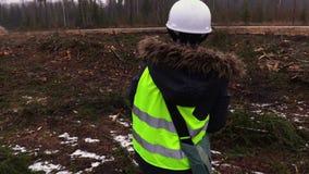 Empleado de sexo femenino de la silvicultura en bosque destruido en día de invierno nevoso almacen de video